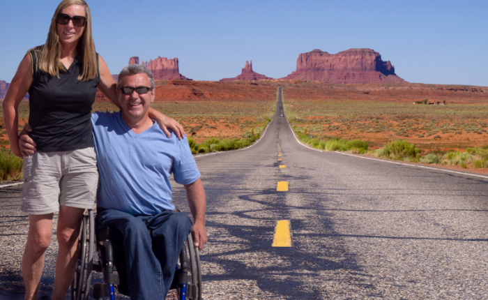 Two travelers, one standing and one in a wheelchair, posed on the road with rock formations behind them