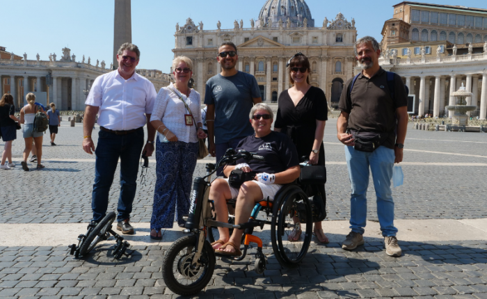 five people standing behind a woman in a wheelchair, all smiling in a plaza in Rome