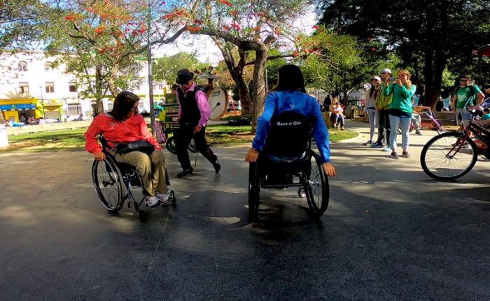 two woman in wheelchairs dancing to a street musiciian playing the drums