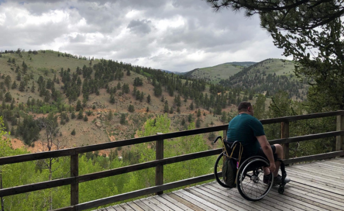 a man in a wheelchair with his back facing the camera on a wood deck overlooking green hills