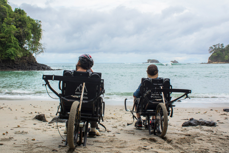 Two wheelchair users with their back to the camera on a tropical beach