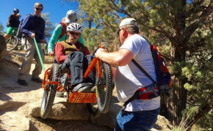 Two men assist a man in a hikiing wheelchair down a steep slope as mountainbikers look on