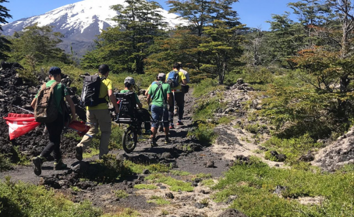 A team of six people, one in a wheelchair, treks through the forest to toward a snow covered volcano.