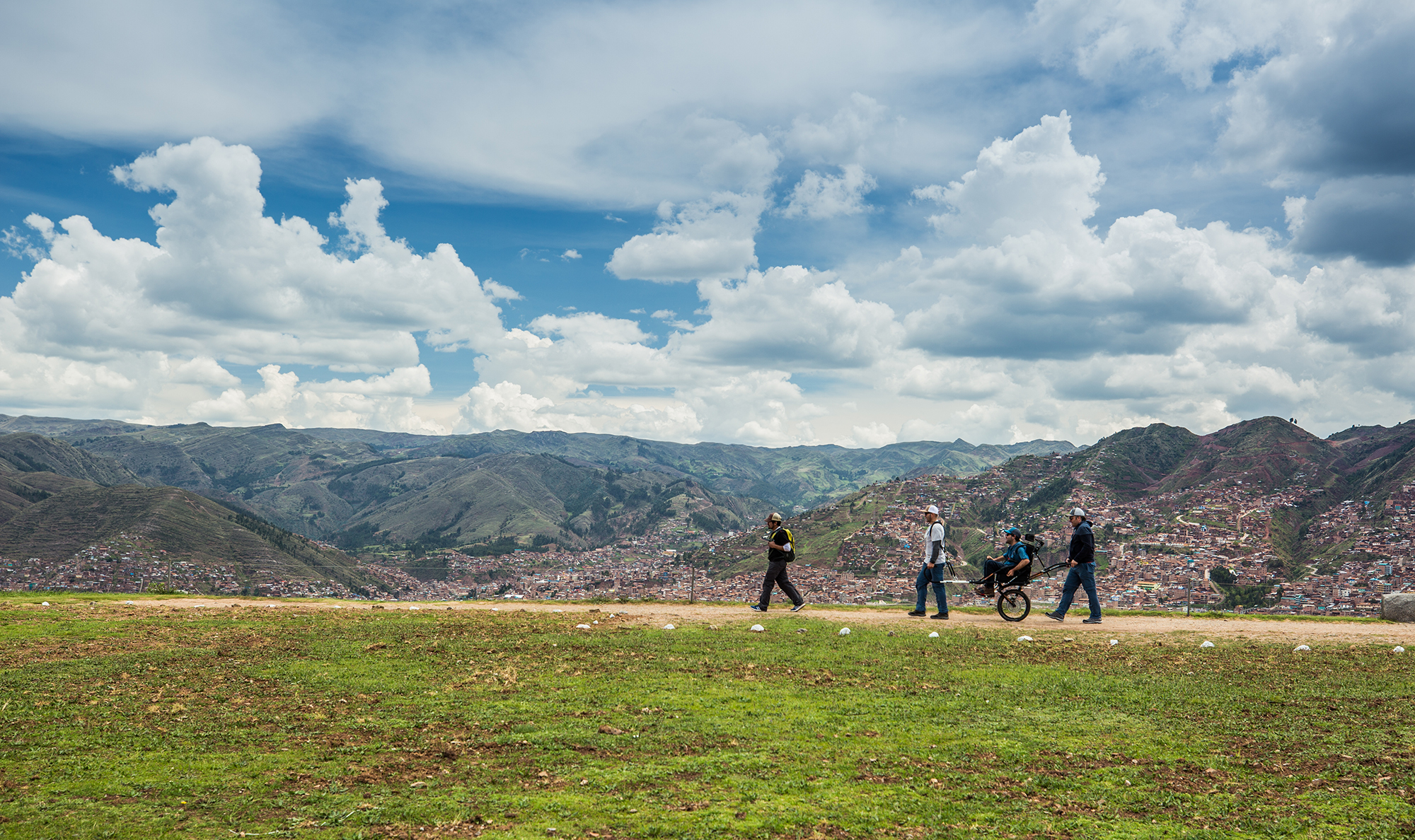 Four people, one in a wheelchair, walk along a pathway in the Sacred Valley on a hill above the town of Pisac