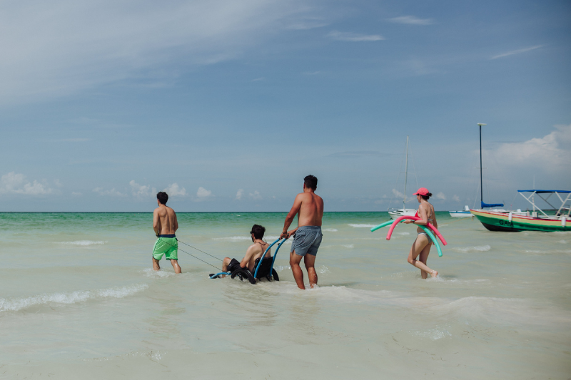 Four people, one in a wheelchair, enter the shallow turquoise ocean