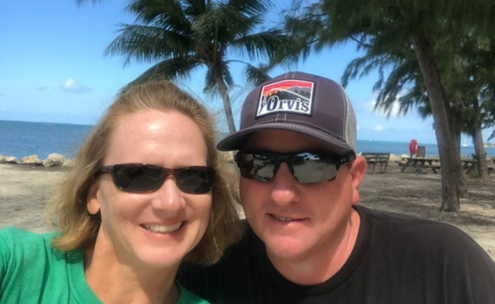 A man and woman take a selfie on the beach with palm trees behind them
