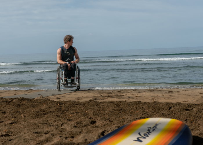 A man in a wheelchair on the beach looks out over the ocean, in the foreground of the photo is the tip of a surfboard