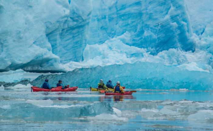 kayakers paddle next to a turquoise colored glacier