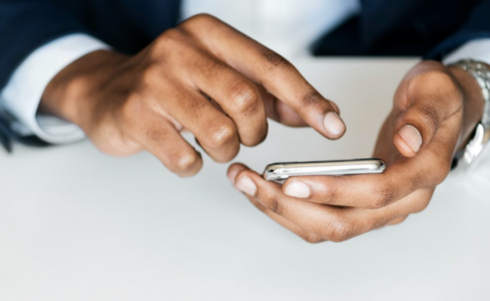the hands of a person in a suit use a smartphone