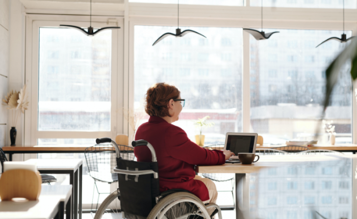 A woman in a wheelchair sits a a table with a coffee, completing remote work on her computer