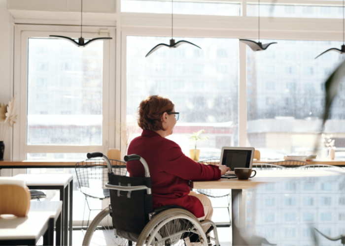A woman in a wheelchair sits a a table with a coffee, working on her computer