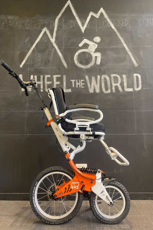 A tall all terrain wheelchair with two wheels and a small seat for children propped up in front of a chalkboard with the Wheel the World log.