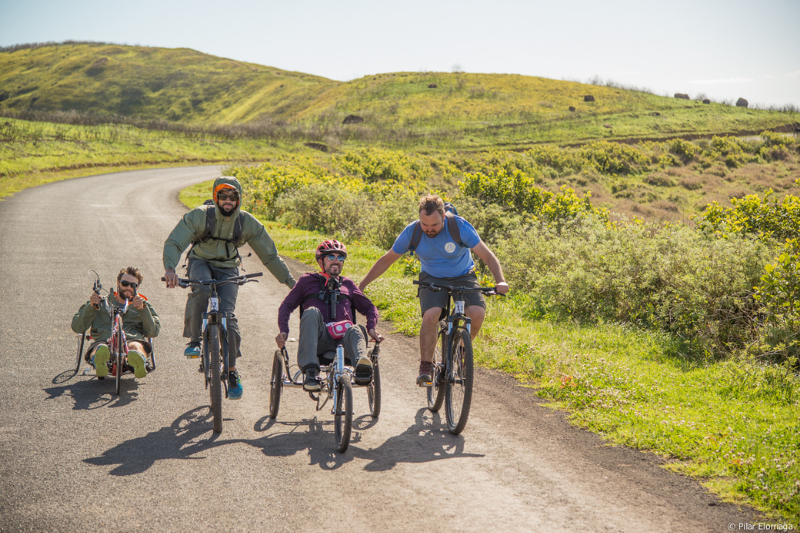 Four men bicycle on a dirt road, bordered by green shrubs. Two are on standard two wheel bikes and two are on adaptive bicycles.