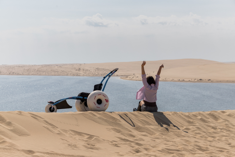 A woman sits on a sand dune looking out onto a lake with her hands in the air and her back facing the camera. An amphibious wheelchair is next to her perched on the dune.