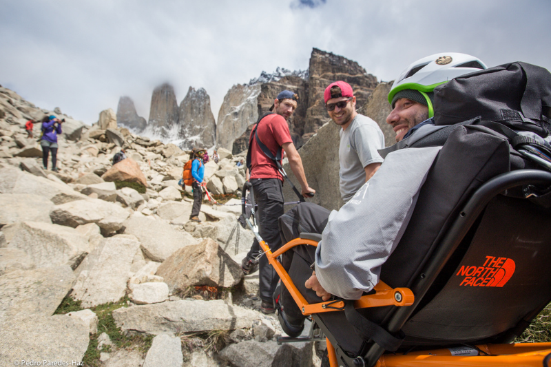 A man in a trekking wheelchair climbs up a trail with the support of two other men. Jagged mountains are in the background and all are smiling.