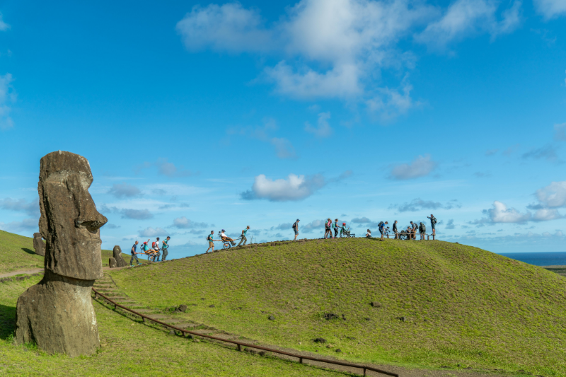 A zoomed out photo of people walking and in wheelchairs next to a Moai statue walking up a hill