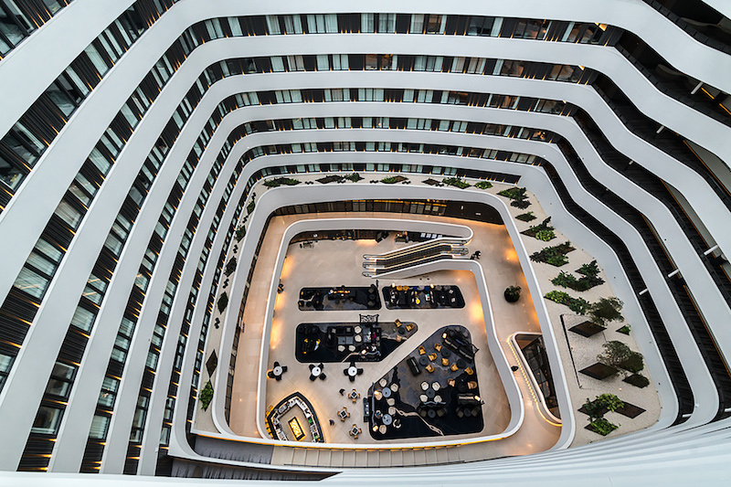 An overhead view of the hotel lobby. The upper floors. of the hotel form a circle around the lobby, creating a courtyard.