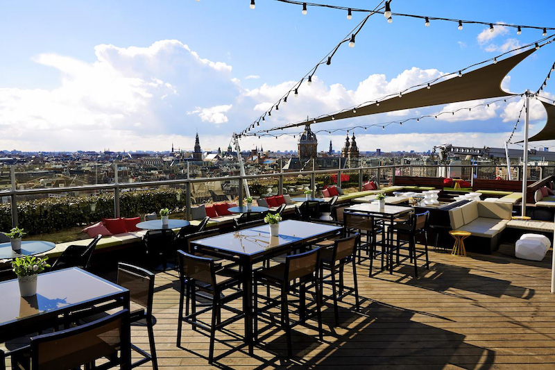 Dining and lounge furniture on a wood rooftop deck with views of the city.